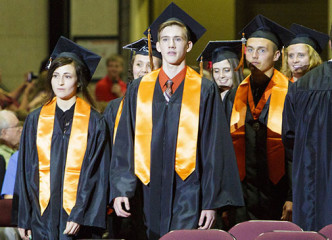Graduates in black, with orange draping ribbons stand up out of their seats