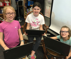 Three young girls lean in working away on laptops