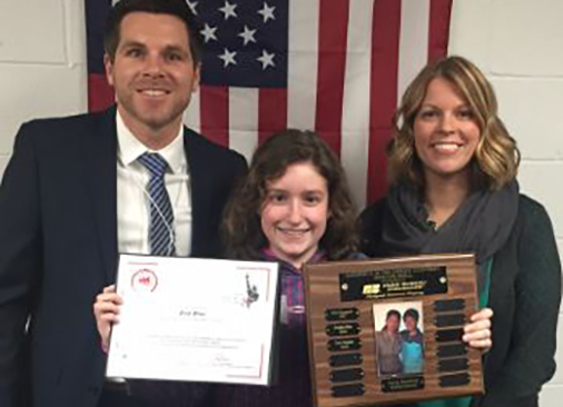 A young girl next to a man and a woman holds up a certificate and a trophy plate