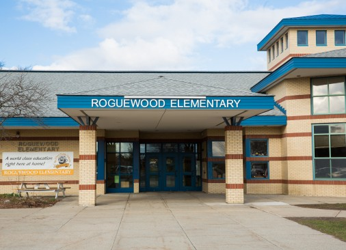 The tall, tan and blue Roguewood Elementary building.