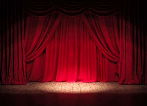 The red curtains on stage glow in the luminosity of the spotlight