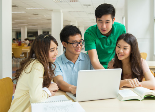 Three students crowd around one of their peers on a laptop