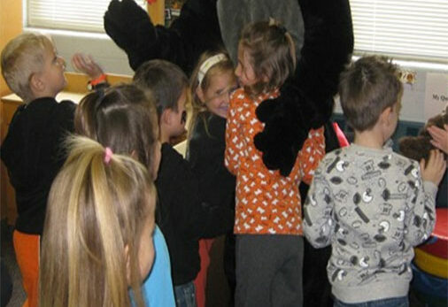 Kids hugging a person in a black cat suit