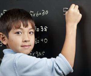 Kid practicing core math on chalkboard