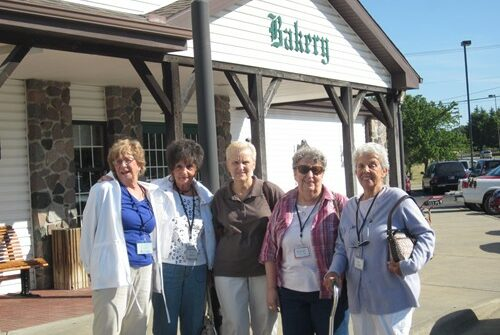 A group of elders group side by side in front of the bakery