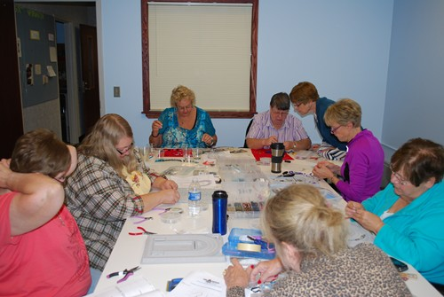 Adults around a table working on crafts