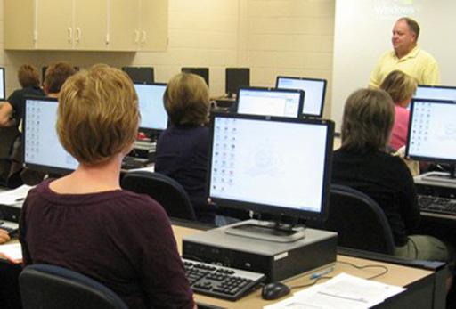 Adults hiding behind computer screens, listen to their teacher wearily