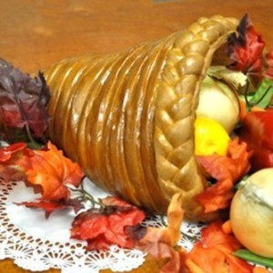 A cornucopia with a surrounding of fall leaves and spewing out fake vegetables
