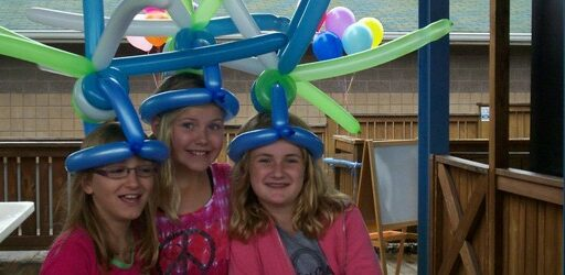 Three girls share a crazy looking balloon hat