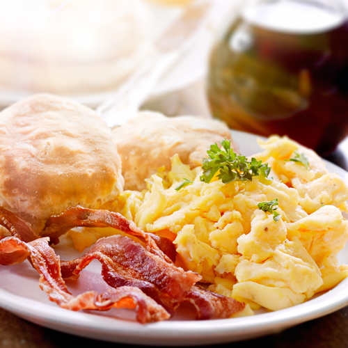 A close up view of a plate of biscuits, eggs, and crispy bacon