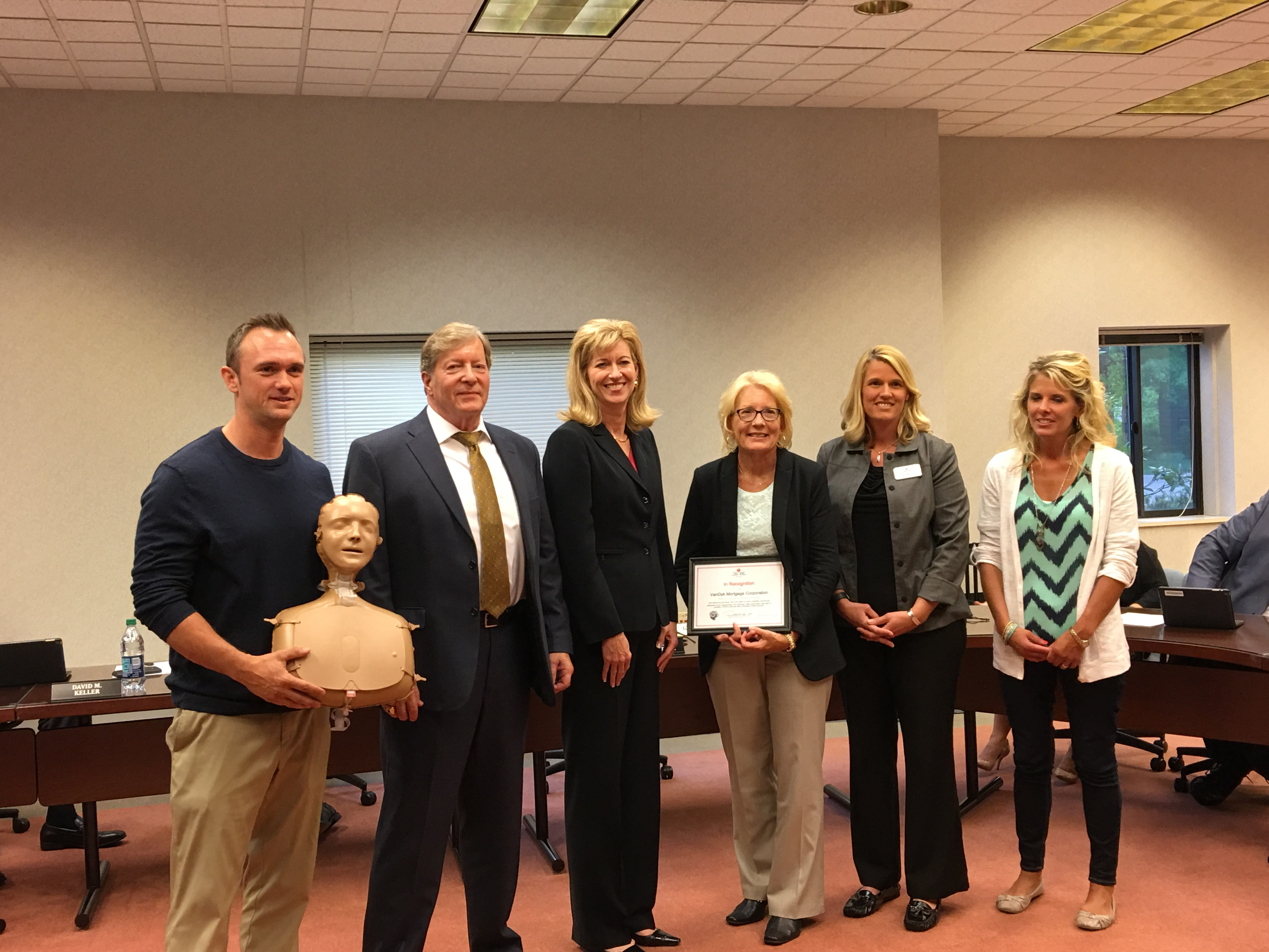 Group photo of AHA and Rockford Public School representatives with inflatable manikin used for CPR training